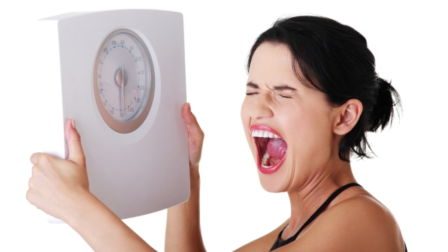 Mujer nerviosa agarrando balanza