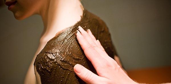 Arcilla aplicada sobre espalda de mujer en Spa