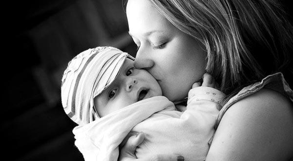 Madre abrazando y besando a su hija en brazos