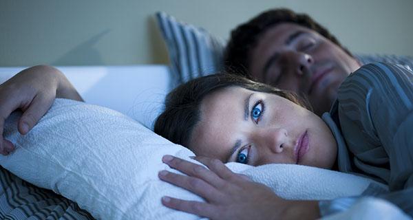 Mujer joven con insomnio en la cama con marido