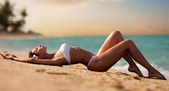 Mujer hermosa tomando sol en la playa
