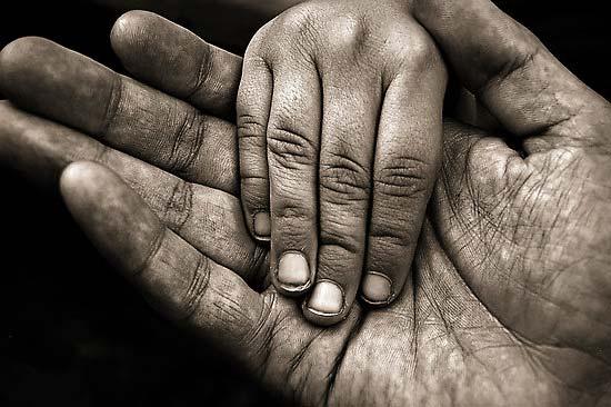 Mano de adulto con mano de un pequeño