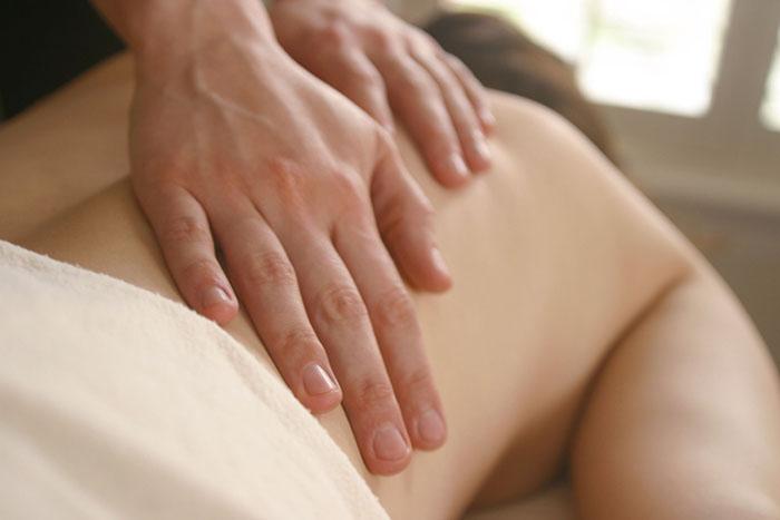 Manos sobre un cuerpo desnudo aplicando ajustes quiropracticos