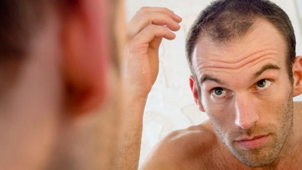 Hombre frente al espejo sufre caída del cabello