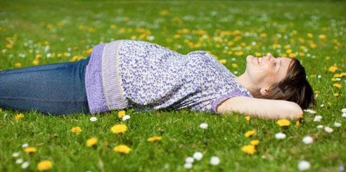 Mujer embarazada en el pasto con flores