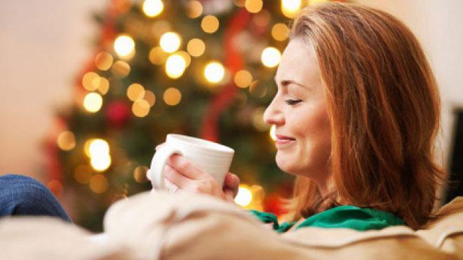 Mujer relajada tomando una taza caliente junto a un árbol de navidad, fin de año