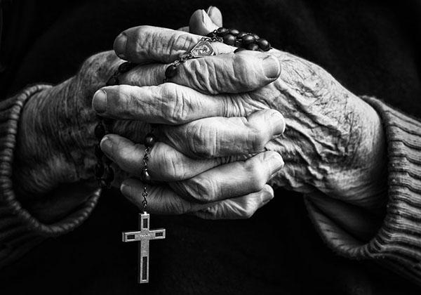Manos arrugadas de anciano con rosario cruz